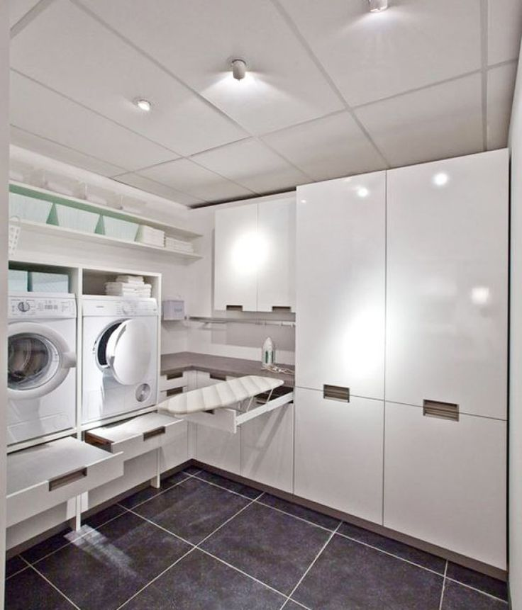 Neste projeto, o piso escuro destaca os armários, brancos, que ocupam todas as paredes - destaque para as máquinas, suspensas
