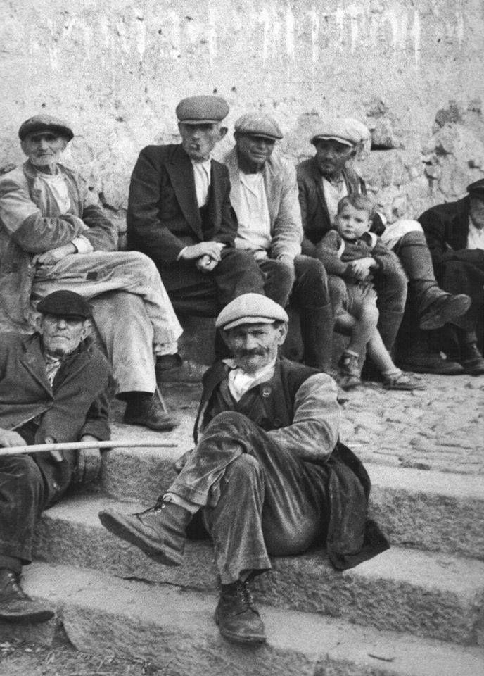 Uomini seduti in piazza a chiaccherare