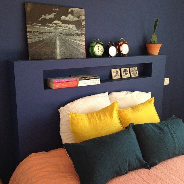 Dark blue wall + contrasted Bright colors bed linen, headboard with niche