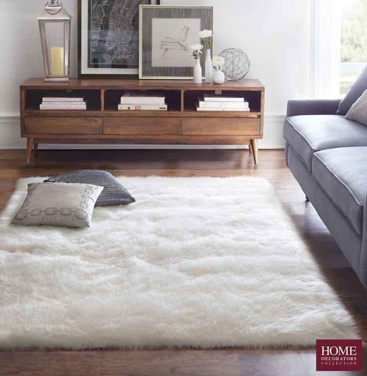 A fluffy rug in the living room... talk about major comfort! Blending beautifully with mid-century modern furniture pieces, this faux sheepskin rug has amazing texture and tons of style appeal. Get the luxurious look of a real sheepskin rug without the high price tag. Our Faux Sheepskin Area Rug is where value meets great style. Refresh your room and try this atop wood flooring for contrasting design. Available at Home Decorators Collection.
