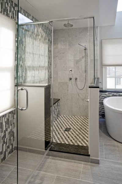 The Frameless Glass Shower Enclosure Features A Marble