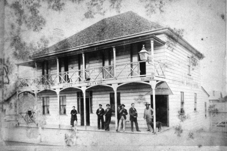 Brisbane Bridge Hotel, Brisbane, ca. 1878 - Erected on the south side of Stanley Street, between Melbourne Street and Russell Street, Brisbane. The hotel was built for Samuel Aburnethy in 1867. When this photograph was taken, John Graham, second from right, was the licensee. In 1888 he erected the palatial Graham's Hotel beside this building.