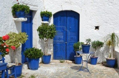 Typical Greek courtyard with blue flower pots in Piskopiano on Crete, Greece. Stock Photo