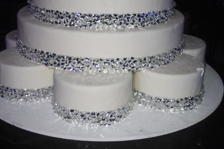 white fondant wedding cake multi-tiered with silver leaf design, crystal strands and rhinestone trim