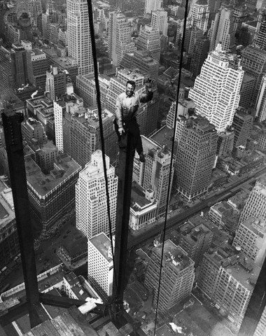 Iron worker Carl Russell waves from the 88th floor of the Empire State Building. September 13th, 1930. Photo from the Bettmann/Corbis Archives.