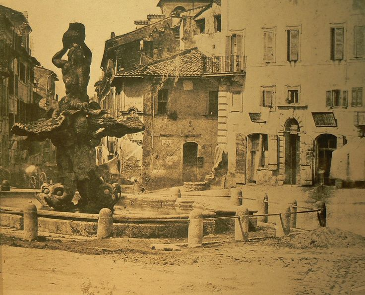 """Su una fotografia del 1855 del celebre Ludovico Tuminello, leggiamo più chiaramente alcune ineguagliabili particolarità degli edifici circostanti la piazza. In particolare, subito a sinistra della Fontana delle Api nella sua collocazione originale, sul muro della casa sull'altro lato della strada, a fianco dell'edicola sacra nascosta dalla conchiglia del Tritone, si vede una vecchia indicazione stradale nella sua primitiva forma 'dipinta' ai primi dell'800, con la scritta: """"Via Felice""""…"""