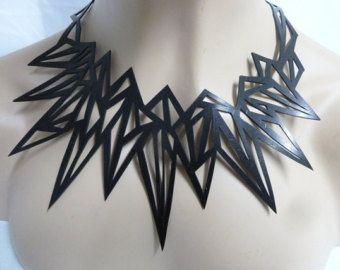 Een handgekapte zwarte rubber ketting, met een abstract ontwerp. Vastgehecht door middel van een ketting aan de achterkant kan heb je het op verschillende lengtes. Aangezien het is hand knippen uniek.