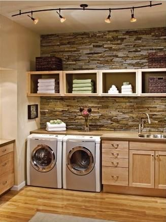 Dream Laundry Room: beautiful rock wall, practical sink, cupboards, and folding space,