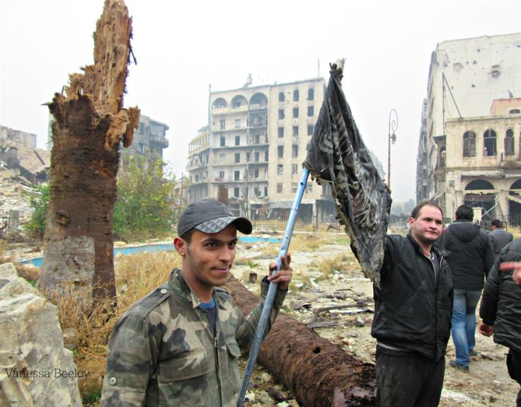Syrian Army soldier holds captured al Nusra Front (al Qaeda) flag in Old City, Aleppo. Click to enlarge