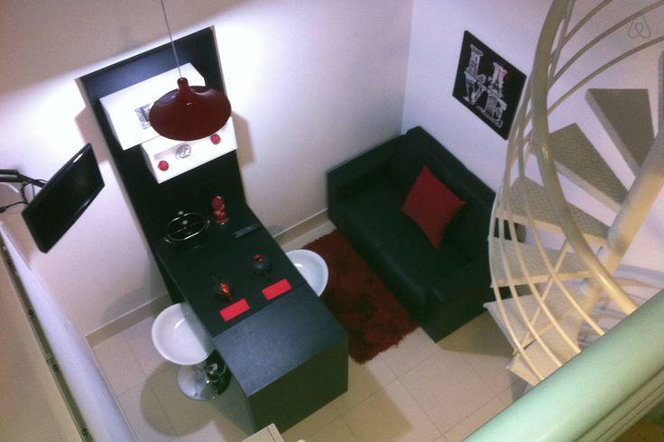 Sala com tv, sofá e mesa dois lugares, vista do quarto
