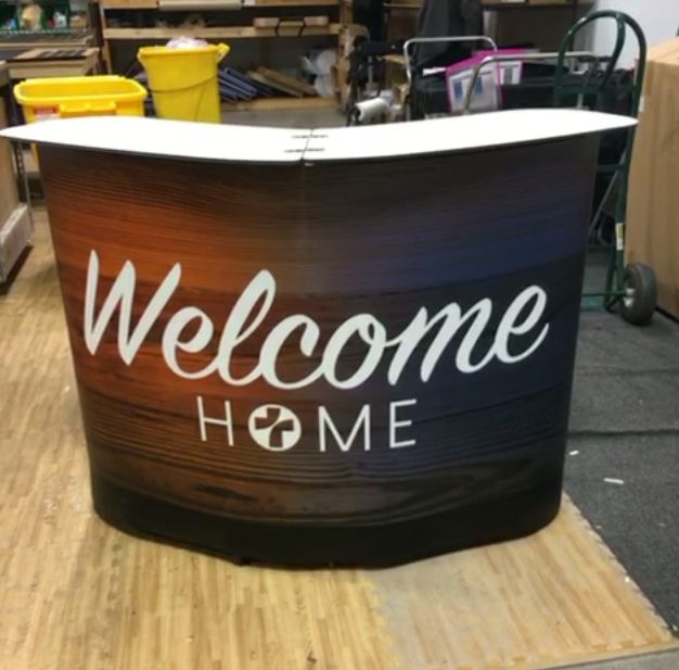 This Large Rolling Case holds tons of stuff, then when emptied, transforms into this counter. Add the custom faux-wood graphic and create a beautiful hospitality desk. (See video on the Displayit at Church Portable Counter Pinterest Page. Central Baptist Church, Round Rock TX.