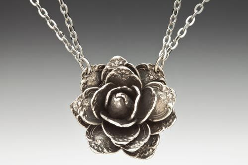 """Rose Spoon Necklace    As one of the most intriquite pieces in our line, the rose necklace is made up of nearly 20 spoon handles!    • Length: 16-18"""" adjustable chain, lobster closure  • Pendant: 1 3/4"""" diameter  • Silver Plate  • Made in the USA   Qty  $69.00"""