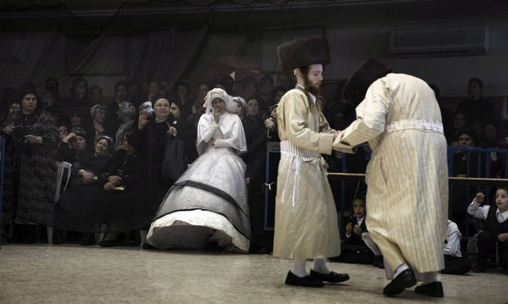 A Jewish groom (center) dances with the Rabbi of the Ultra-Orthodox Jewish group, Tholdot Avraham Yizhak Hasidic, as his bride watches during their wedding in Mea Shearim, an Ultra-Orthodox neighborhood of Jerusalem on Aug. 28. During the Mitzva Tanz dance ritual, members of the community and family dance in front of the bride at the end of the wedding ceremony. (Menahem Kahaha/AFP/Getty Images