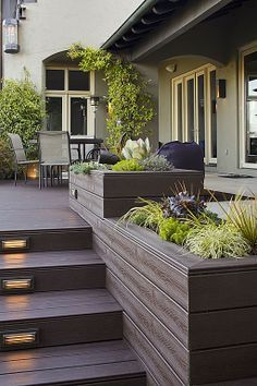 Planters constructed of the same wood used for the deck tie this backyard garden look together. #patio #flower #floor