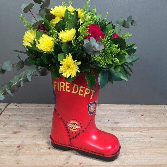 Σύνθεση σε μεταλλικό κασπώ κόκκινη μπότα πυροσβέστη με κόκκινα τριαντάφυλλα, κίτρινα χρυσάνθεμα, σολιντάγκο και διάφορες πρασινάδες.Στο κάτω μέρος στα προτεινόμενα βλέπεται το κασπώ που χρησιμοποιήθηκε για αυτή τη σύνθεση.http://nedashop.gr/anthopoleio/gennisi?product_id=879