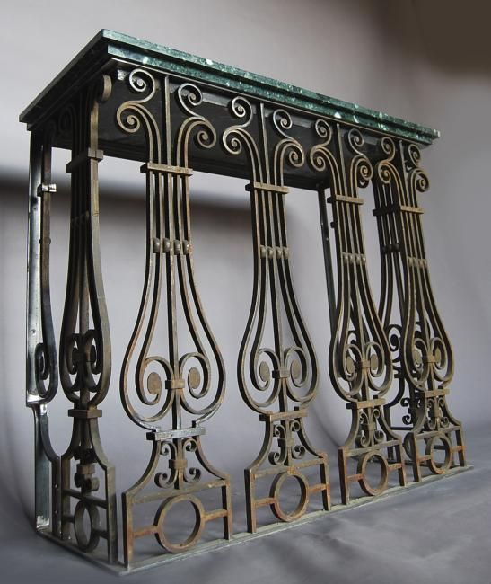 a steel wrought iron and marble topped console table