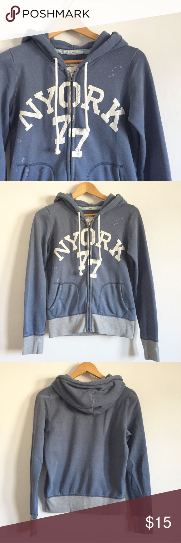AE Blue NY Zip Up Sweatshirt Cute and cozy zip up sweatshirt from American Eagle. Light blue, white letters and stitching,and splattered bleach spots. Size small, 85% cotton, 15% polyester. Pre-lived, great condition! American Eagle Outfitters Tops Sweatshirts & Hoodies