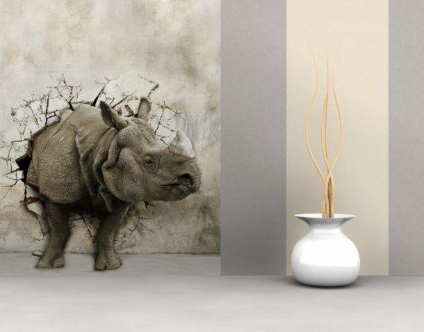 Fotobehang met neushoorn die door de muur heen breekt.