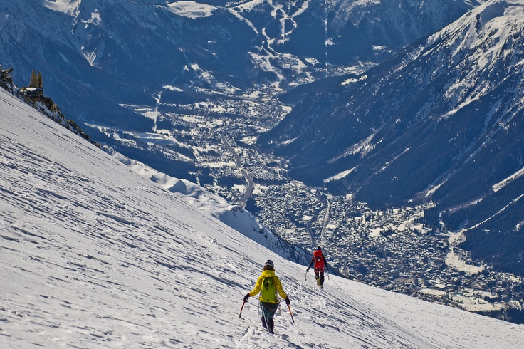 A group of climbers descends the Glacier des Grands Montets with a spectacular view on Chamonix Valley. Photograph taken during winter climbing session in Chamonix, Mont Blanc, France.