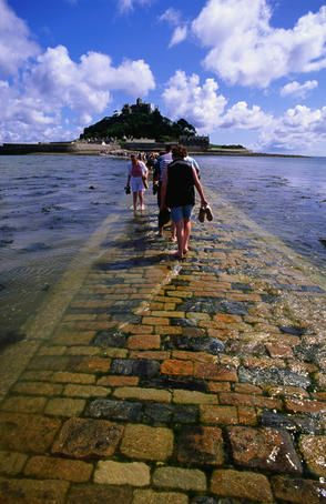 Crossing the causeway to St Michael's Mount, Cornwall, England, with tide rolling in.