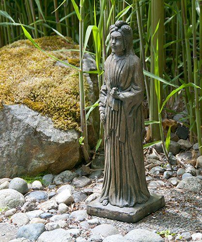 Kuan Yin. Stained ornamental concrete statue for Japanese garden or outdoor patio .