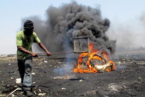 Au Ghana, un homme brûle la mousse isolante d'un réfrigérateur pour récupérer les pièces de celui-ci. Une activité à hauts risques sanitaires, mais traditionnelle dans certains pays en voie de développement. © DR
