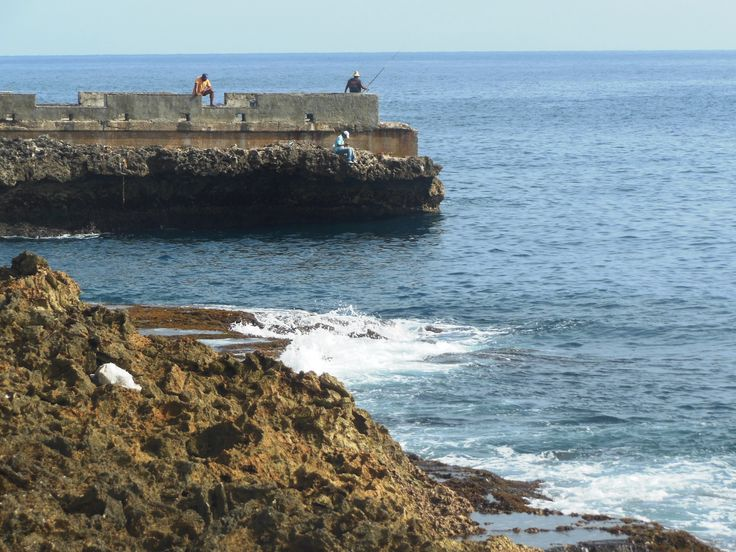 The malecon or seawall stretches along the north shore of the city where the Atlantic surf crashes. Fisher fellows through their lines off the distant dock. (Photo by Kathryn MacDonald© at www.travelnotebook.ca)