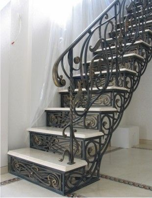 Лестница с кованым косоуром и мраморными ступенями.