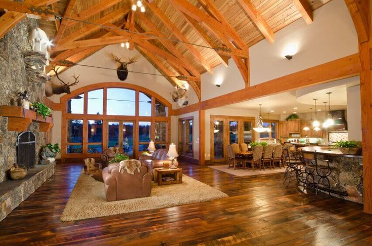 This enormous open plan living room boasts a strong country cabin feel, with mounted animal busts and a massive stone fireplace. The vaulted ceiling is supported by warm wood exposed beams.