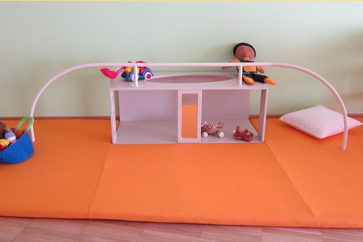 First Steps Unit. Handrail to support first steps for babies and toddlers. Possible to crawl through the unit, stand up inside, see multiple reflections and look through coloured windows, suggesting ways to pause, experiment and interact with other children.