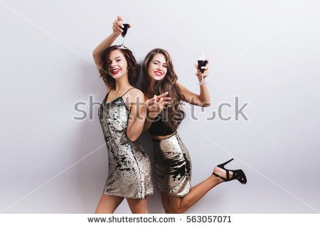 Beautiful girls, two friends smiling and raising glass of red wine, having fun. Wearing dresses with sequins, girl has leg up with high heels sandal. Sexy, stylish look. Isolated