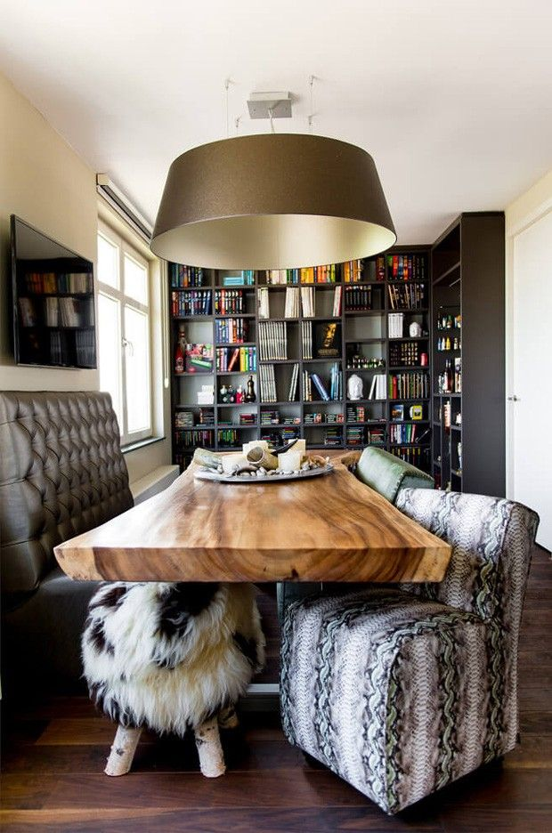 Sala de jantar com estante e TV. Mesa e piso de madeira, poltronas com mix de estampas, banquinho de pele sintética