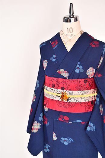 ネイビーブルーの地にブルーとレッドとカラフルチェックのお花模様が織りだされたウールのアンサンブル(着物と羽織のセット)です。