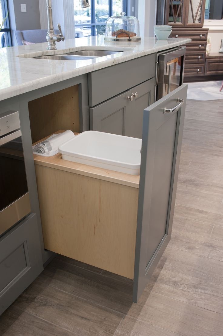 Pull out garbage can Design by Dalton Carpet One Wellborn Cabinets- Finish: Back Wall - Maple Glacier; Island - Willow Door Style: Messina Countertops: Caesarstone Fresh Concrete; Calcutta Latte Floor Tile: Logwood Grey Grout: Mapei Pewter Photo by: Dennis McDaniel