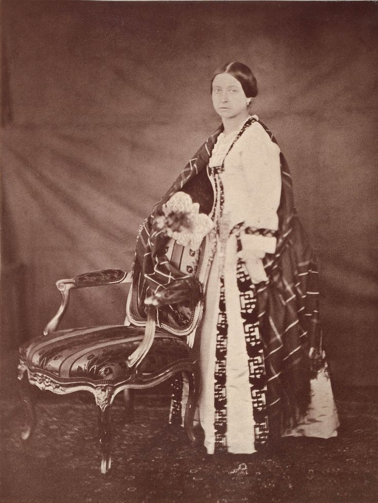 Queen Victoria.   Creator: After Roger Fenton (1819-69) (photographer)  Creation Date: after an original of 8 Feb 1854  Materials: Printed in carbon by Mullins in 1889  Dimensions: 21.1 x 15.9 cm  RCIN   2906507  Provenance: Commissioned by Queen Victoria in 1854  Description: Photograph showing full length portrait of Queen Victoria taken at Windsor Castle. She has her hands placed on the back of a chair and wears a cloak over a her dress.