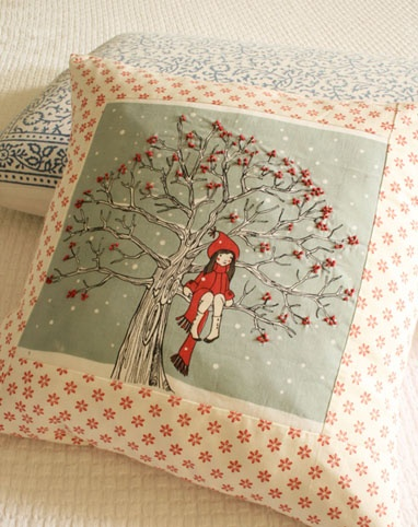 A beautifully embroidered pillow: a girl sitting on a tree.