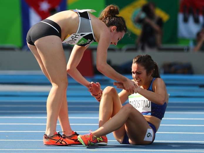 Nikki Hamblin of New Zealand stops running during the race to help fellow competitor Abbey D'Agostino of the USA after D'Agostino suffered a cramp in the 5,000m heats at the Rio Olympics August 16, 2016.