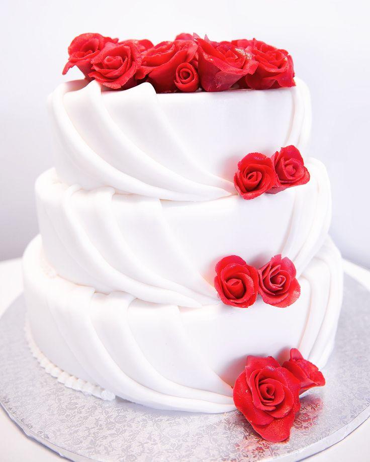 Eine edle dreistöckige Torte garniert mit roten Rosen.  #Hochzeitstorte #Blumen #Rosen #rot #schlicht #elegant #3stöckig #Sommer #weiß #weddingcake #roses #flowers #red #love