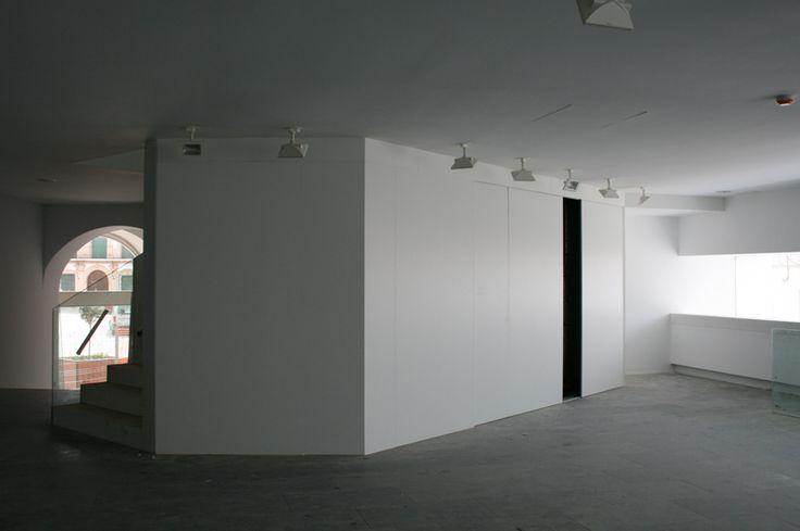 Revestimiento de pared lacado en blanco con puertas correderas integradas.