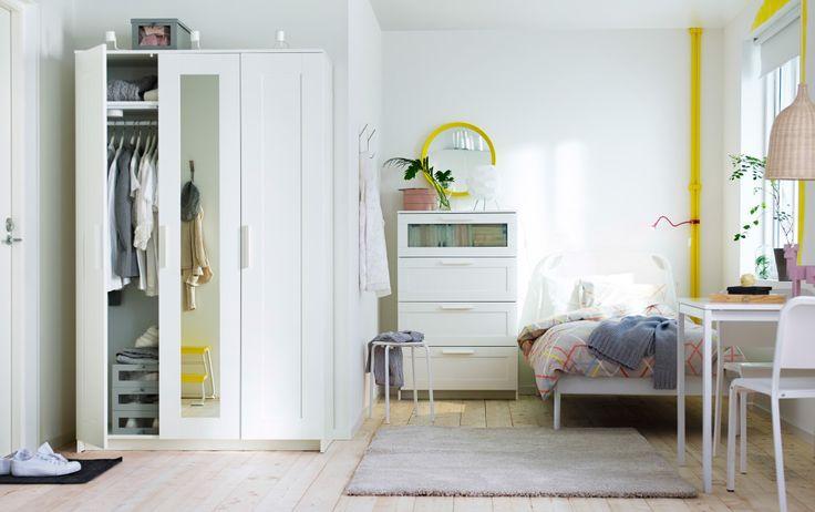 Um pequeno apartamento com um roupeiro, cómoda, cama, mesa pequena e duas cadeiras, tudo em branco.