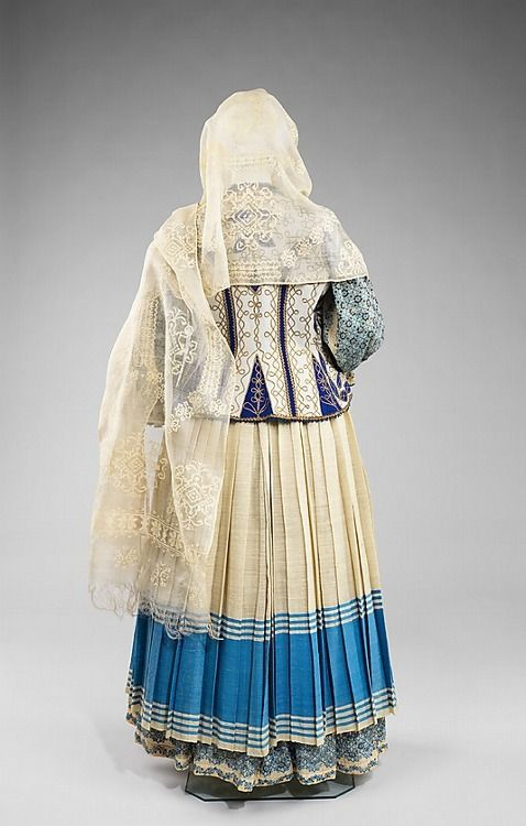 """1875-1900 Romanian folk costume The basic model for women consists of an embroidered blouse and skirt, belt, head scarf, and often a vest or jacket. As in many cultures, embroidery is placed at """"vulnerable"""" areas of the body: the neck, cuffs, and hem, but also at the shoulders and sleeves as a symbol of strength. MET"""