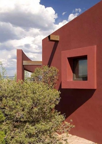 Flat-roofed house in Santa Fe uses scuppers instead of roof drains and internal downspouts. When using this sort of scupper, it's recommended to consider how the water hits the landscape