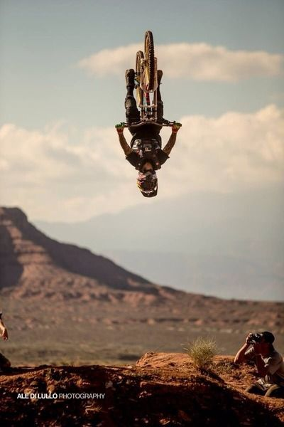 Downhill mountain bike rider doing an awesome back flip over a bike dirt jump.
