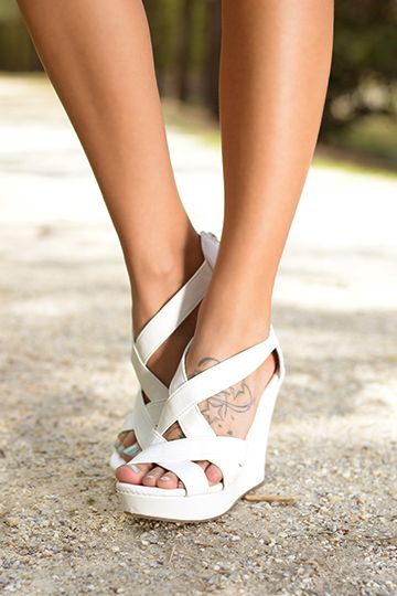We think this white wedge is the perfect way to complete any spring or summer outfit! The crossing straps foot comfortable and securely over the top of your foot in a totally adorable way! We think these wedges look great with sundresses! :) Fits true to size.