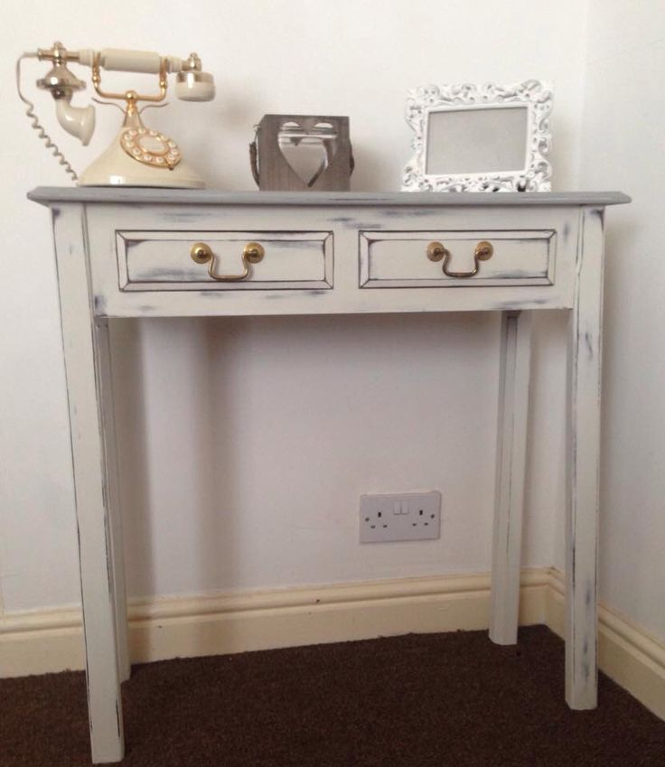 Beautiful console table. Painted in Old White with a Paris Grey top. There is also a consistent highlight of Old White throughout the top too. Distressed for a vintage look and waxed for a protection from heat and moisture with clear wax. Left the original gold handles for an antique contrast.