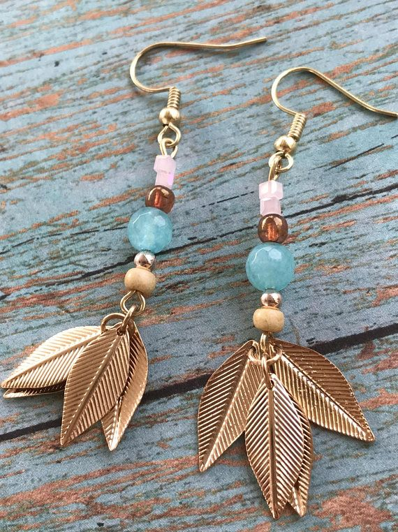 Handmade drop earrings on gold tone fish hook earrings. Lightweight feather charms and glass beads dangle from fish hooks. Earrings are very lightweight and hang approx. 2 1/2 long.