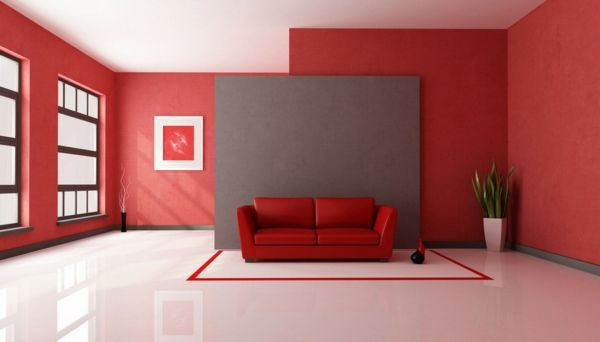 Rotes Sofa vor grauer Wand in rotem Raum.