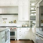 kitchens - stainless steel barrel range hood pot filler open shelves glass canisters glass-front fridge white shaker kitchen cabinets kitchen island microwave oven white porcelain farmhouse sink