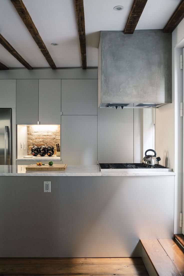 The kitchen range hood is framed in wood, wrapped with cement board, and parged with a thin layer of polished concrete. The sides of the Carrara-topped island are clad in anodized aluminum, as are the IKEA cabinets.