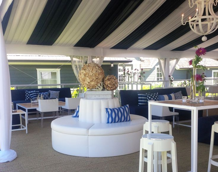 L-eat Catering goes nautical with this wedding reception, and hosted at a lakehouse it made perfect sense! Navy and white circus-style fabric ceiling, crisp white seating, plexi tables and patterned pillows decorate this outdoor space.